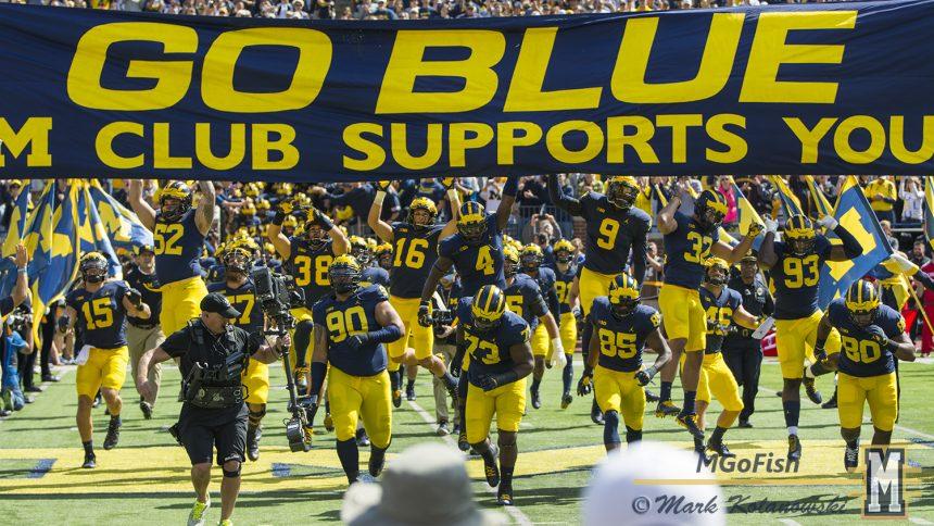 2017 Michigan football team touching the banner in pregame of the season opener against Cincinnati at Michigan Stadium in Ann Arbor, Michigan on September 9th, 2017. Photo: Mark Kolanowski/MGoFish