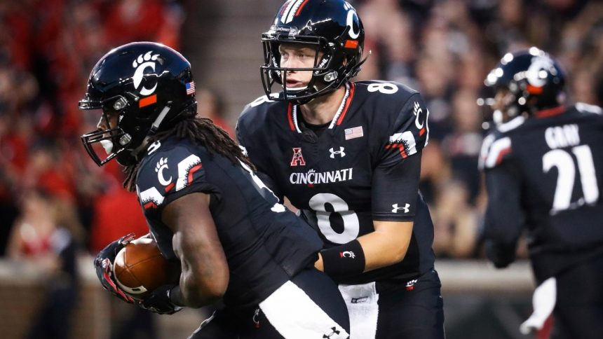 Cincinnati quarterback Hayden Moore hands off the ball to running back Mike Boone, left, during the first half of an NCAA college football game against Houston, Thursday, Sept. 15, 2016, in Cincinnati. (AP Photo/John Minchillo)