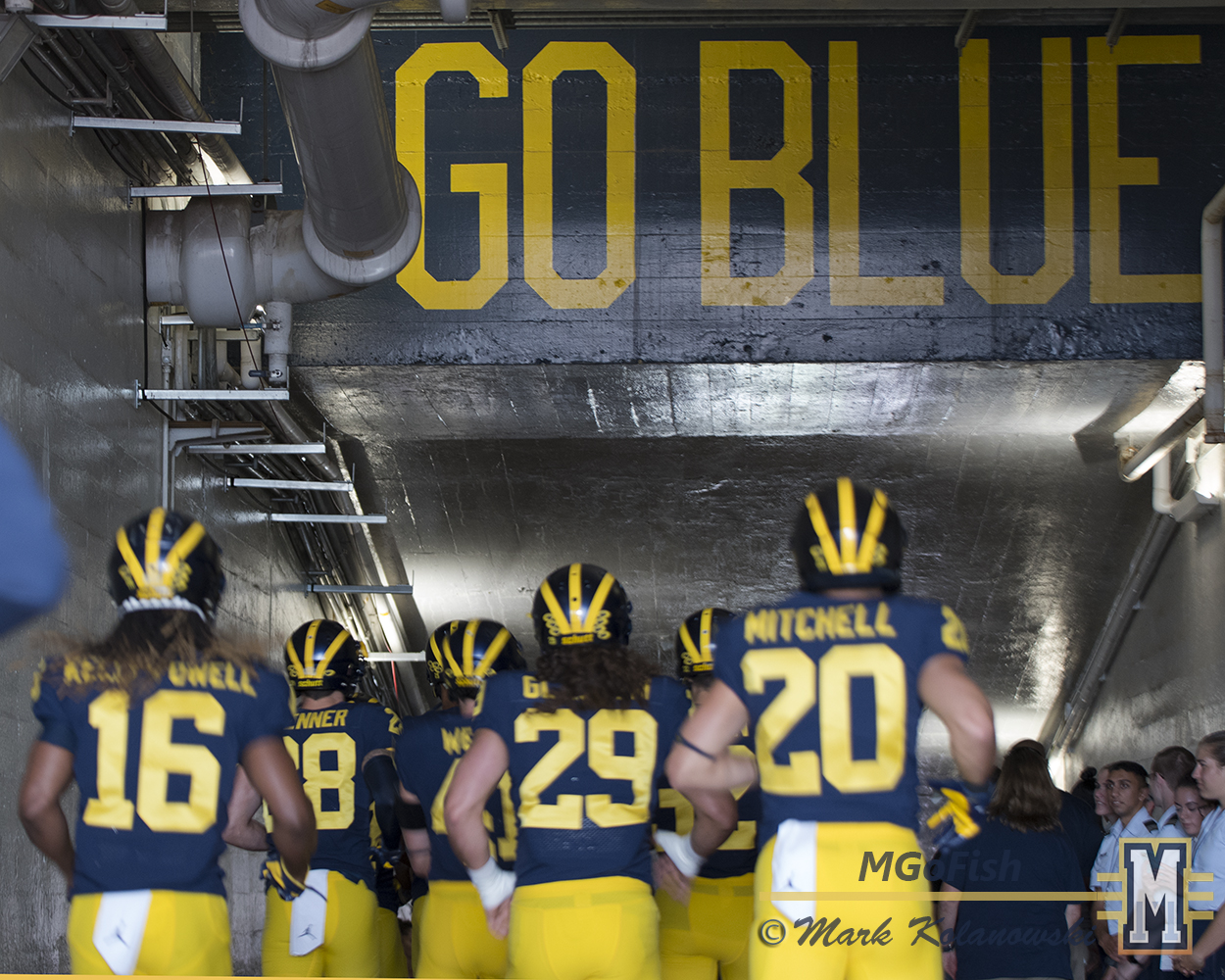 Michigan players running down the Big House tunnel under the Go Blue signs. Photo: Mark Kolanowski/MGoFish