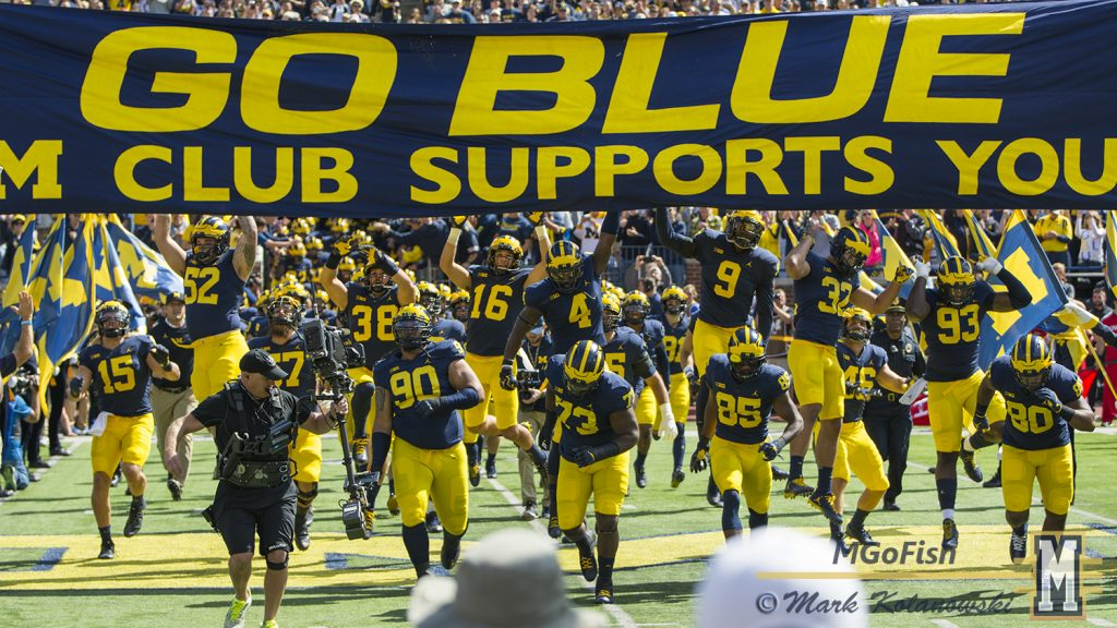 2017 Michigan football team touching the banner in pregame of the season opener against Cincinnati at Michigan Stadium in Ann Arbor, Michigan on September 9th, 2017. Photo: Mark Kolanowski/MGoFish